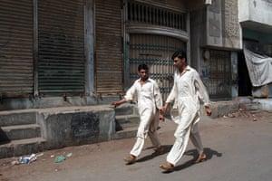 Karachi Pakistan: Men walking in Lyari, one of the oldest neighbourhoods in Karachi