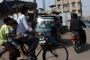 Karachi Pakistan: Vehicles and cyclists on the road in Lyari