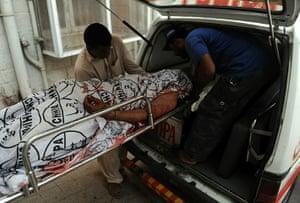 Karachi Pakistan: Pakistani volunteers carry an unidentified bullet-riddled body