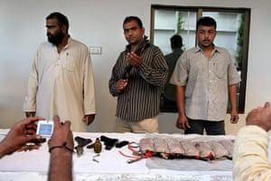 Karachi Pakistan: Karachi police officers show weapons and an explosives vest
