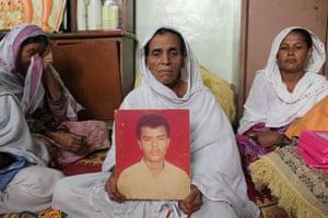 Karachi Pakistan: Jan Bibi holds a photo of her 30-year-old son Rehman Baloch, who was killed