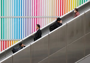 24 hours in pictures: People ride an escalator outside a railway station in Tachikawa