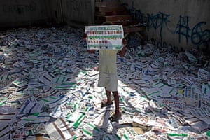 24 hours in pictures: A child holds up an unmarked election ballot, Haiti