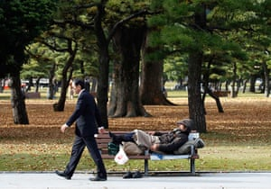 24 hours in pictures: A homeless man sleeps on a bench at a park in Tokyo