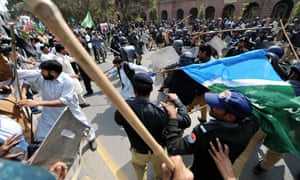 Pakistani riot police and opposition party activists clash at an anti-government protest in Lahore