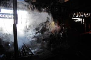 From the agencies: A steel worker is pictured as he cools machinery with water