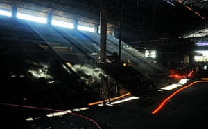 From the agencies: A steel worker is pictured as he works with molten steel