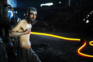 From the agencies: A steel worker is pictured as he washes