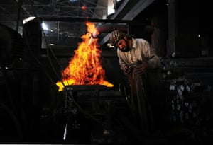 From the agencies: A steel worker is pictured in front of a furnace