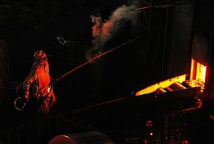 From the agencies: A steel worker removes a block of molten