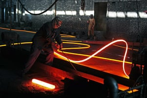 From the agencies: A steel worker works on molten steel shaping