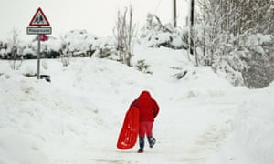 A girl trudges with a sledge through snow in Dunning in Perthshire