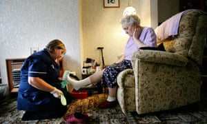 carer putting slippers on elderly woman sitting in armchair