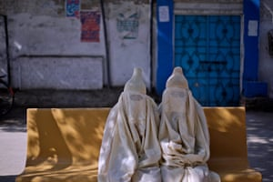 24 hours in pictures: Pakistani floods displaced women sit on a bench outside the hospital