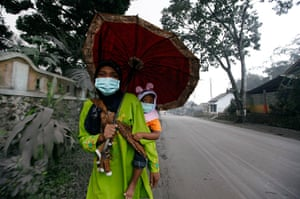 24 hours in pictures: A mother carries her child as she walks down an ash-covered street