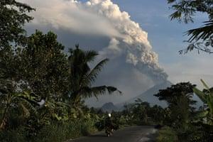 Mount Merapi: A motorist rides as Mount Merapi spews thick ashes