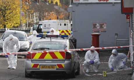 Forensic officers examine the scene of the bomb attack in west Belfast