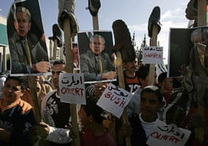 George W Bush: 19 December 2008: Palestinian demonstrators hold placards topped with shoes
