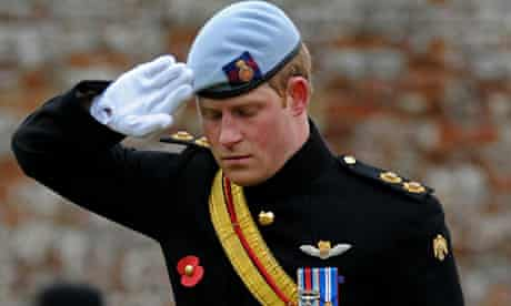 Prince Harry salutes after laying a cross of remembrance in memory of his friends