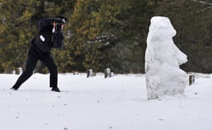 Snow today: A Parks Police officer takes photographs of a snowman in Richmond Park