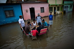 24 hours in pictures: People play dominos in a flooded street in Higuerote, Venezuela