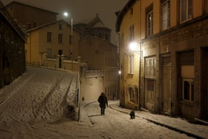 24 hours in pictures: A woman walks with her dog as snow falls in Lyon
