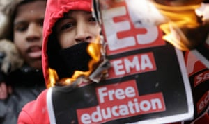 24 hours in pictures:  A banner is burnt as students take part in a protest over budget cuts