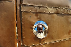 24 hours in pictures: Child stands in the inside courtyard of the preschool he attends in Kibera