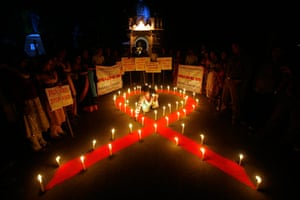 24 hours in pictures: Activists from an NGO light candles during AIDS awareness campaign