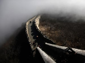 24 hours in pictures: Tourists walk along a section of the Great Wall shrouded in mist at Simatai