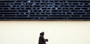 24 hours in pictures: A woman passes by pigeons on the grid of a subway ventilation system