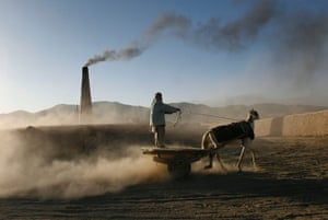 24 hours in pictures: An Afghan man rides on his horse drawn cart to collect bricks