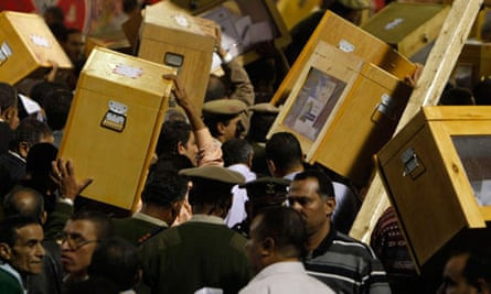 Police officers carry ballot boxes during Egypt's parliamentary elections