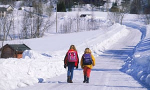 Two school children with backpacks on country road in winter in Scandinavia