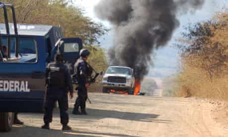 A car suspected to belong to hitmen burns in the outskirts of Apatzingan