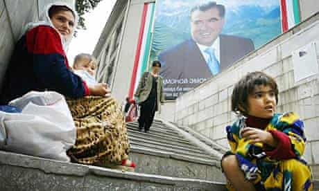 A mother and her children beg in front of a picture of Tajik president Emomali Rakhmonov in Dushanbe