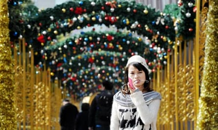 A woman talks on her mobile phone under Christmas decorations in Shanghai