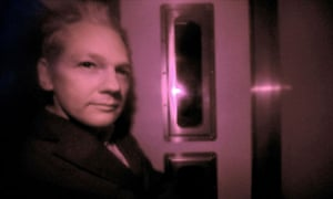 Julian Assange, pictured through the heavily tinted windows of a police vehicle