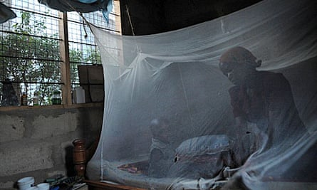 A mother and child sit under a mosquito net in Tanzania