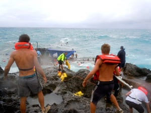 Christmas Island: People clamber on the rocky shore on Christmas Island during rescue attempt