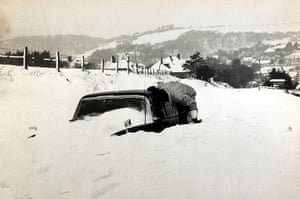 1962 Winter Freeze: A man peers into a car to check if there are occupants inside