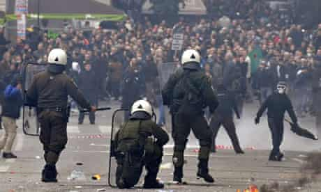 Demonstrators face riot police in Athens today.