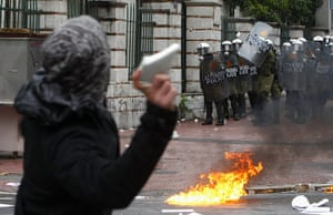 Riots in Athens: A protester throws a rock at riot policemen during protests in Athens