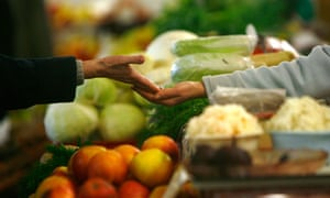 A customer pays after buying produce at a market in Riga, Latvia