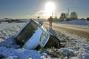 Winter Weather Europe: A man walks towards a car which ended up