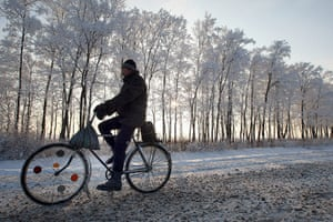 Winter Weather Europe: A man rides his bike on a snow-covered r