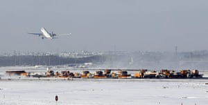 Winter Weather Europe: Snowploughs clear runways as a plane takes off after snowfall at Frankfurt