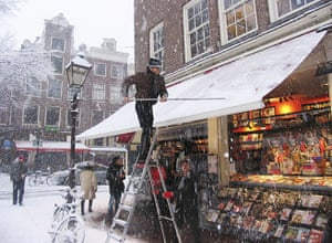 Winter Weather Europe: A man removes snow from an awning of a bookstore in Amsterdam's city center