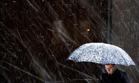 A man with an umbrella walks during a snowfall in London