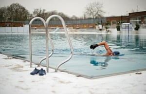 Snow: A man swims in an unheated outdoor lido